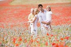 Familie die zich in papavergebied het glimlachen bevindt Stock Fotografie