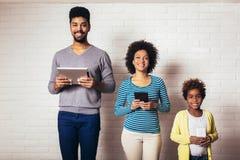 Familie die zich voor een bakstenen muur bevinden en een digitale tablet en telefoons houden royalty-vrije stock foto's