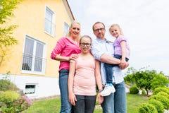 Familie die zich voor huis of huis bevinden Stock Fotografie