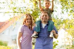 Familie die zich voor huizen bevindt Stock Foto's