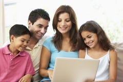 Familie, die zu Hause auf Sofa mit Laptop sitzt lizenzfreies stockbild