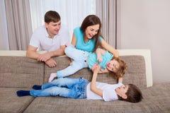 Familie, die zu Hause auf Sofa spielt lizenzfreies stockbild