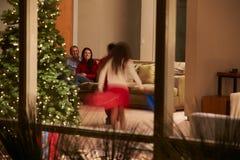 Familie, die zu Hause das Weihnachten angesehen von O feiert lizenzfreie stockbilder