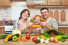 Familie, die zu Hause im Kücheninnenraum, in den frischen Obst und Gemüse in kocht Gesundes Nahrungsmittelkonzept Frau, Mann und  Lizenzfreie Stockfotografie