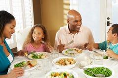 Familie, die zu Hause Mahlzeit genießt stockbild