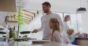 Familie, die zu Hause Nahrung in der Küche 4k zubereitet stock footage