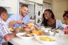 Familie, die zu Hause um die Tabelle isst Mahlzeit sitzt stockfoto