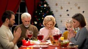 Familie, die zu Hause vor Mahlzeiten, traditionelles Weihnachtsessen, Dankbarkeit betet lizenzfreie stockfotos