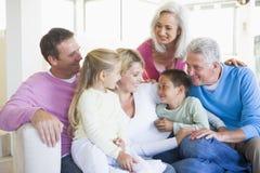 Familie, die zuhause lächeln sitzt Stockbilder
