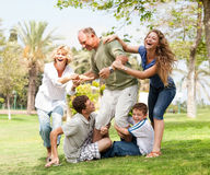 Familie, die zurück Großvater anhält und Spaß hat Lizenzfreie Stockfotos