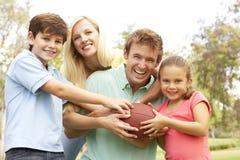 Familie, die zusammen amerikanischen Fußball spielt Lizenzfreie Stockfotos