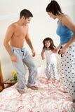 Familie, die zusammen auf Bett aufprallt Stockbild