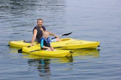Familie, die zusammen auf einem schönen See Kayak fährt Stockbilder