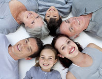 Familie, die zusammen auf Fußboden mit Köpfen liegt Stockfotografie