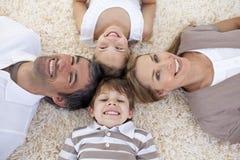 Familie, die zusammen auf Fußboden mit Köpfen liegt lizenzfreies stockbild