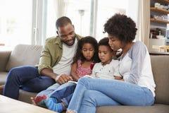 Familie, die zusammen auf Sofa In Lounge Reading Book sitzt lizenzfreie stockbilder