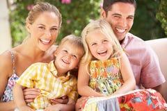 Familie, die zusammen auf Sofa sitzt Lizenzfreie Stockbilder