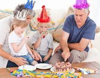 Familie, die zusammen den Geburtstagkuchen isst Stockbild