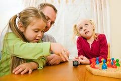 Familie, die zusammen ein Brettspiel spielt stockfotos