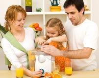 Familie, die zusammen frischen Fruchtsaft bildet Lizenzfreies Stockfoto