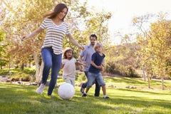 Familie, die zusammen Fußball im Park spielt Stockbild