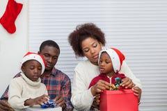 Familie, die zusammen Geschenk zusammenbaut Stockbilder