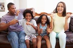 Familie, die zusammen im Sofa Watching Fernsehen sitzt lizenzfreie stockfotos
