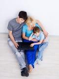 Familie, die zusammen Laptop betrachtet Stockfoto