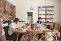 Familie, die zusammen Mahlzeit in der Großraumküche isst lizenzfreie stockfotos