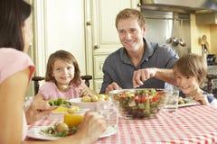 Familie, die zusammen Mahlzeit in der Küche isst lizenzfreies stockfoto