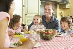 Familie, die zusammen Mahlzeit in der Küche isst stockfotografie