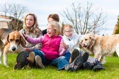 Familie, die zusammen mit Hunden auf einer Wiese sitzt Lizenzfreies Stockfoto