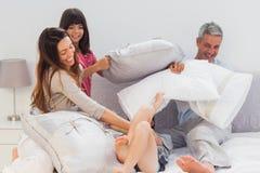 Familie, die zusammen mit Kissen auf Bett kämpft Stockfoto
