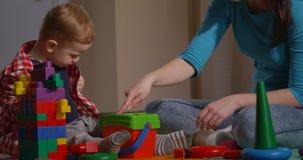 Familie, die zusammen Mutter und Kind mit Spielwaren und Bausteinen spielt stock video