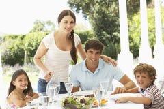 Familie, die zusammen outisde isst Stockbild