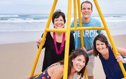 Familie, die zusammen um eine Struktur auf dem Strand aufwirft Lizenzfreie Stockfotos