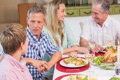 Familie, die zusammen am Weihnachtsabendessen spricht Lizenzfreies Stockbild