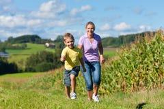 Familie draußen läuft auf eine Wiese Lizenzfreies Stockbild