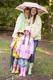 Familie draußen im Regen mit dem Regenschirmlächeln Lizenzfreie Stockfotos