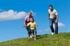 Familie draußen läuft auf eine Wiese Stockfotos