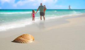 Familie durch Seashell auf tropischem Strand Stockbild