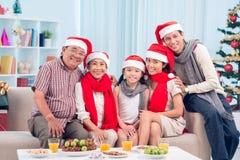 Familie durch Weihnachtstabelle Stockfotografie