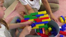 Familie eine Wand von buntem von Spielziegelsteinen errichten stock video