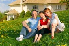 Familie an einem Haus Stockbild
