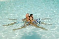 Familie in einem Swimmingpool Stockfotografie