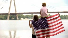 Familie eingewickelt in der amerikanischen Flagge, die Brücke, Immigration für besseres Leben betrachtet lizenzfreie stockfotografie