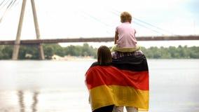Familie eingewickelt in der deutschen Flagge, die Brücke, Immigration, Unabhängigkeitstag betrachtet lizenzfreie stockfotografie