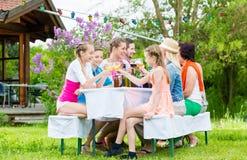 Familie en buren bij tuinpartij het drinken Stock Foto's