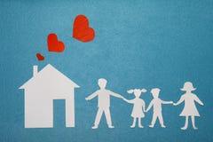 Familie en huisliefdeconcept Document huis en familie op blauwe geweven achtergrond Papa, mamma, dochter en zoonsgreephanden royalty-vrije stock foto's