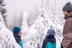 Familie en sneeuwman in het bos van de de wintersneeuw stock afbeeldingen